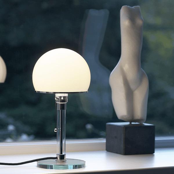 La lampe bauhaus WG24 de Wilhelm Wagenfeld allumée, répondant une lumière douce diffuse