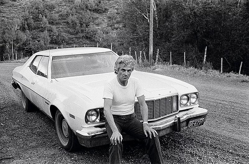 portrait du designer Pierre Paulin assis sur une voiture