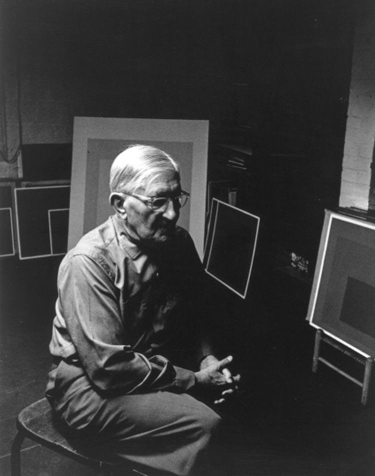 """Portrait de Josef Albers assis dans son atelier de peinture avec ses tableaux """"hommage au carré"""""""