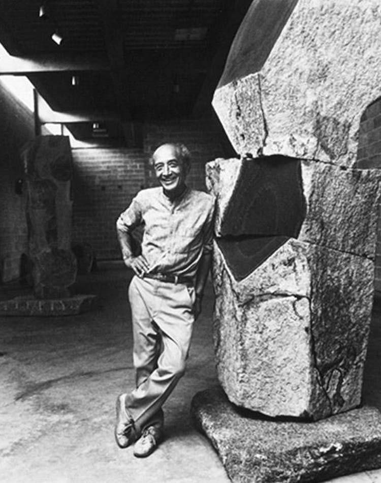 Isamu Noguchi posant à côté de son oeuvre