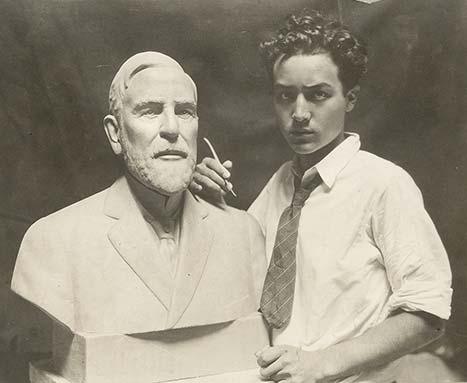 Isamu Noguchi à côté d'une sculpture d'un buste