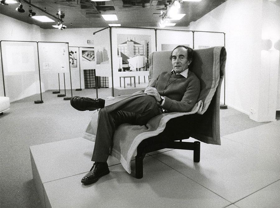 Vico Magistretti assis dans un fauteuil à une exposition